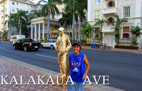 カラカウア通りの歩道にいる大道芸人と記念写真