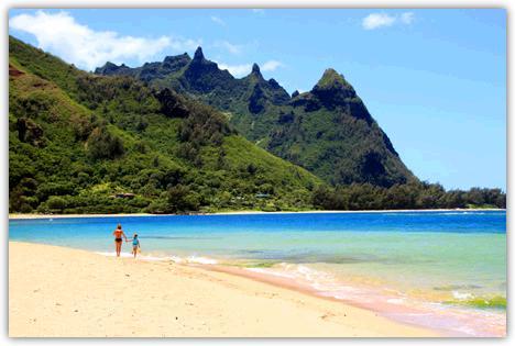 カウアイ島のハエナビーチ。白い砂浜を親子が手をつないで歩いている。