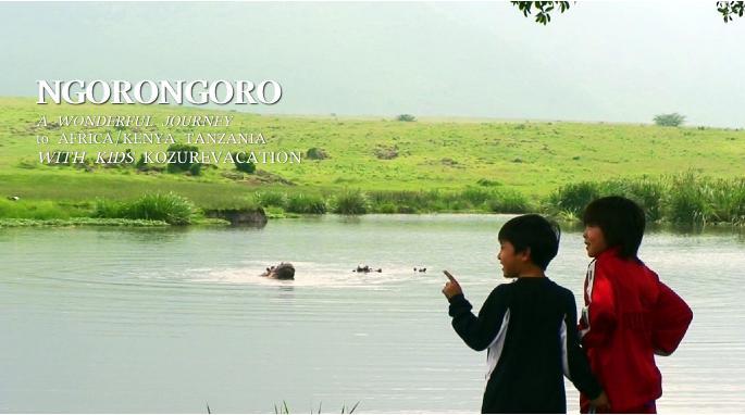 池の中のカバを眺める子供達