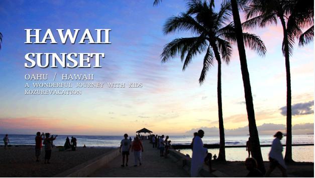 クヒオビーチの桟橋ワイキキウォールとハワイの夕暮れの写真。赤紫色の空とヤシの木のシルエットが写っている。