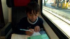 電車の中で宿題をするリュウ