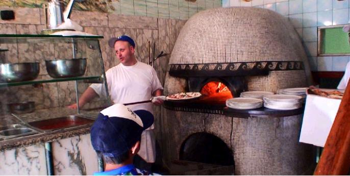 焼き上がったピザを薪窯から取り出す