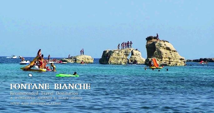 沖の岩から飛び込む人々
