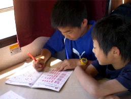 キャンピングカーの移動中に勉強する子ども達