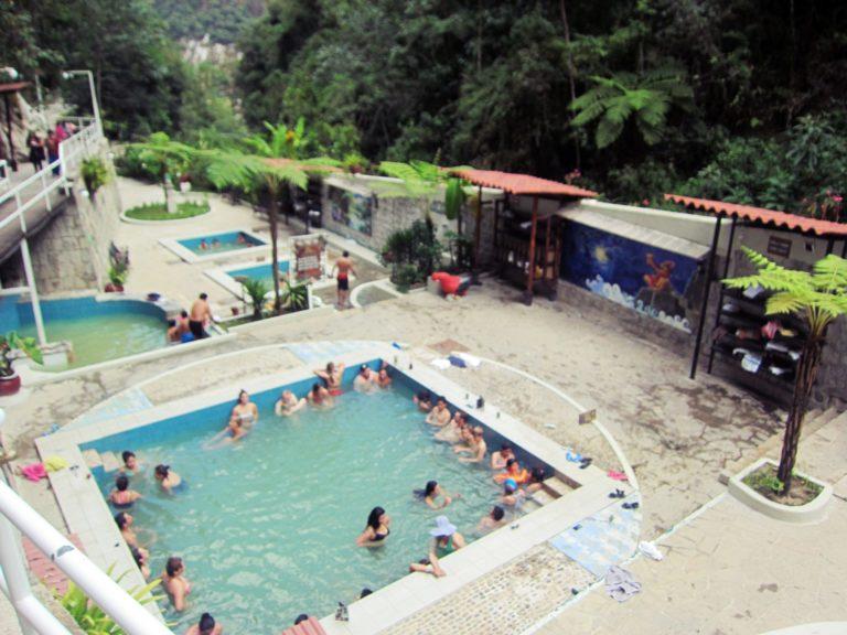 マチュピチュ温泉の写真。山に囲まれた場所にいくつかの露天風呂があり多くの人が水着で入浴している。