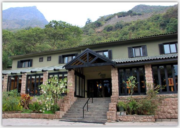 ベルモンドサンクチュアリロッジマチュピチュの正面写真。階段に続く玄関とレストラン、2階の客室が写っている。さらにホテルの背後にはマチュピチュ山の見える。