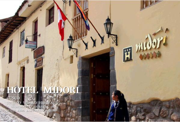 クスコのホテルミドリ。エントランスの上には2つの旗が掲げてある。クリーム色の壁が続く2階建ての建物でホテルの入り口前を紺色に制服を着た少女が歩いている。