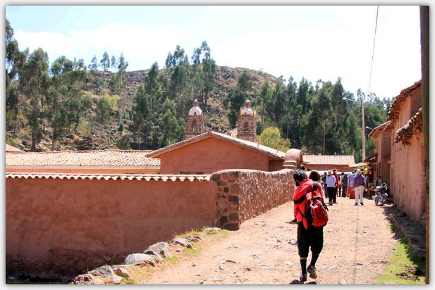 赤い土壁が続く砂利道を歩く長男。