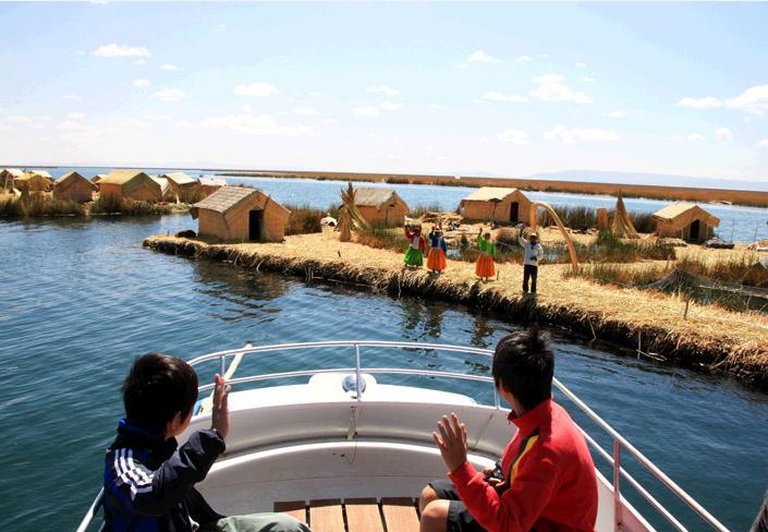 船の上から島民に手を振る子ども達