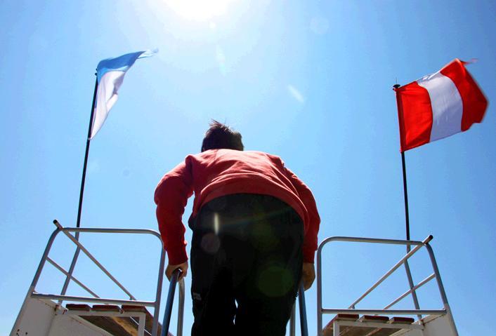 屋上のテラス席にはしごを使って登る長男。船の屋根にはペルーとボリビアの国旗がはためいている。