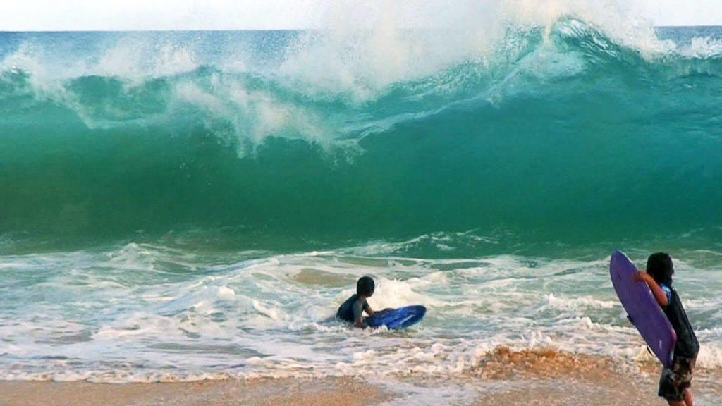 サンディービーチでボディボードを楽しむ子ども達