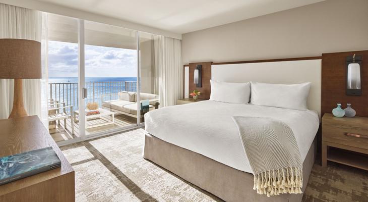 オーシャンビューの客室。キングサイズベッドと窓の外のラナイの先には海が見えている。