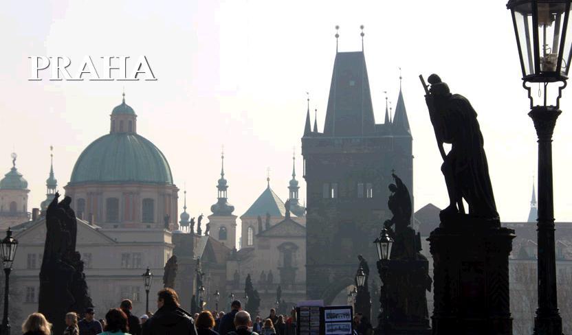 プラハ、カレル橋の写真。聖者の銅像が並ぶ先にいくつもの塔がそびえている。橋の上には大勢の観光客がいる。