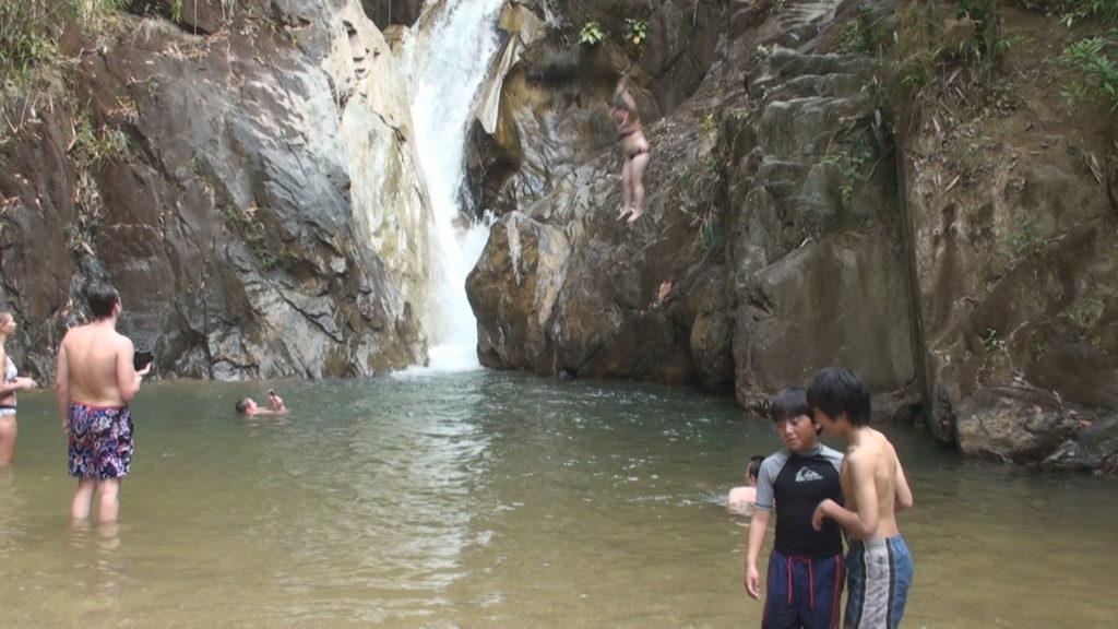 滝壺に飛び込む女性と淵の前で話し込む長男と次男