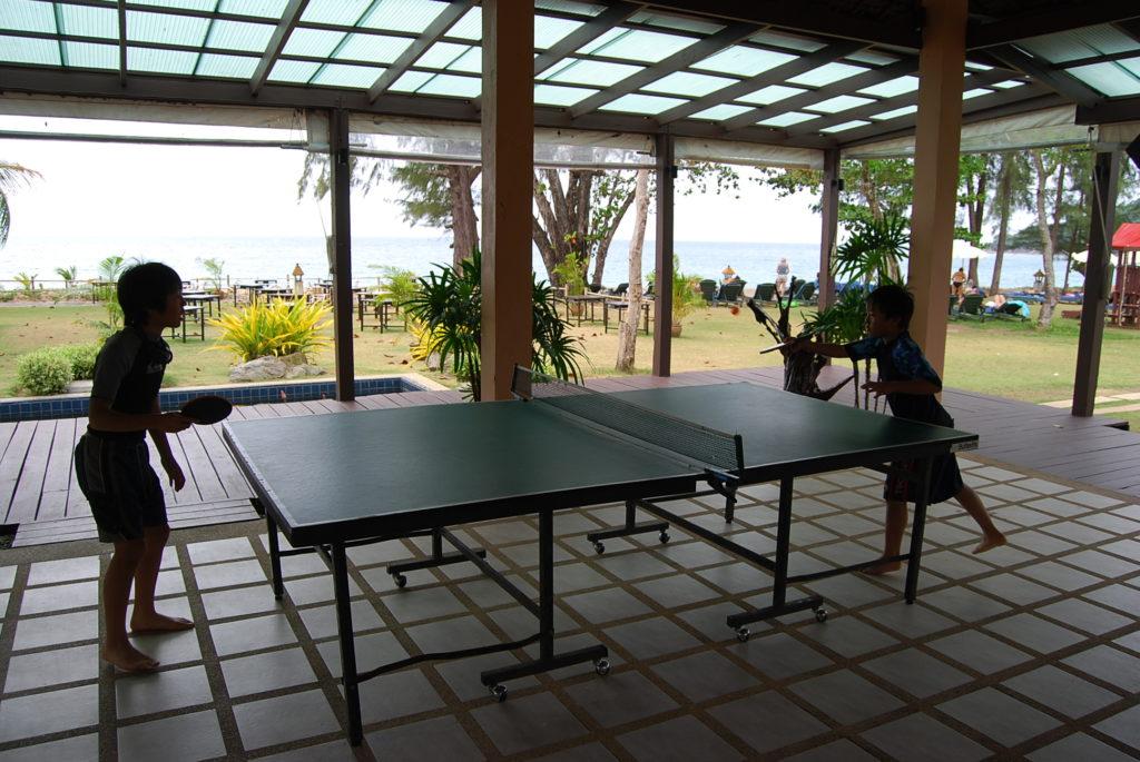 ビーチ沿いのプレイルームで卓球をする子供達