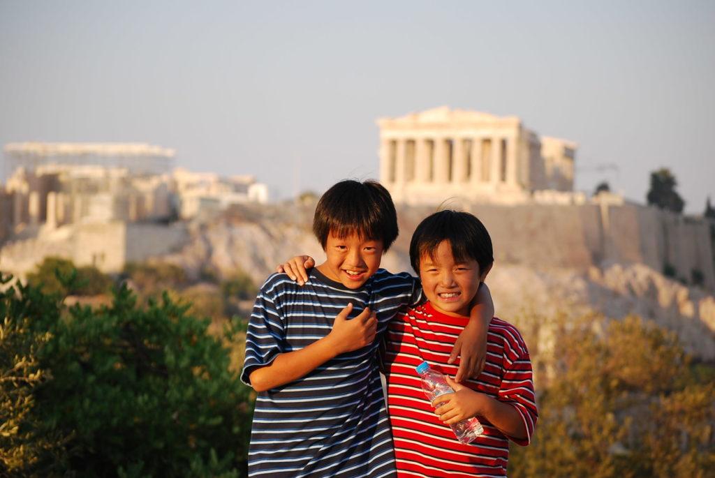 夕日に染まるパルテノン神殿を背景にした子供たちの写真