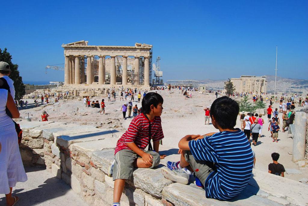 パルテノン神殿を眺めながら座ってお話する子供たち