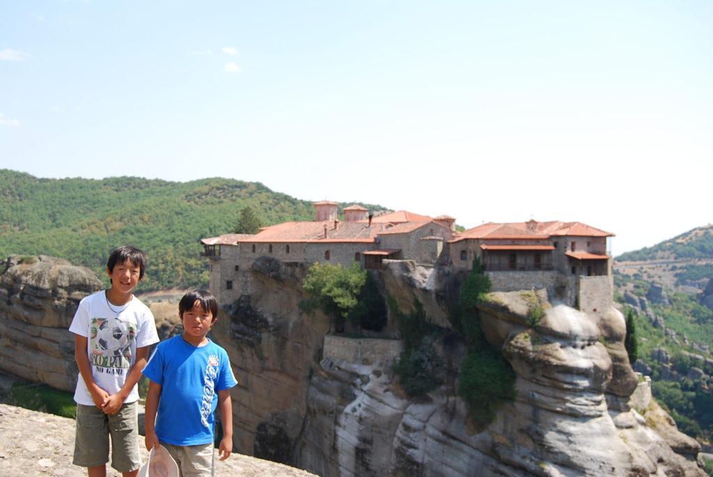 岩山の頂上に立つ修道院を背景に撮影した長男と次男の記念写真