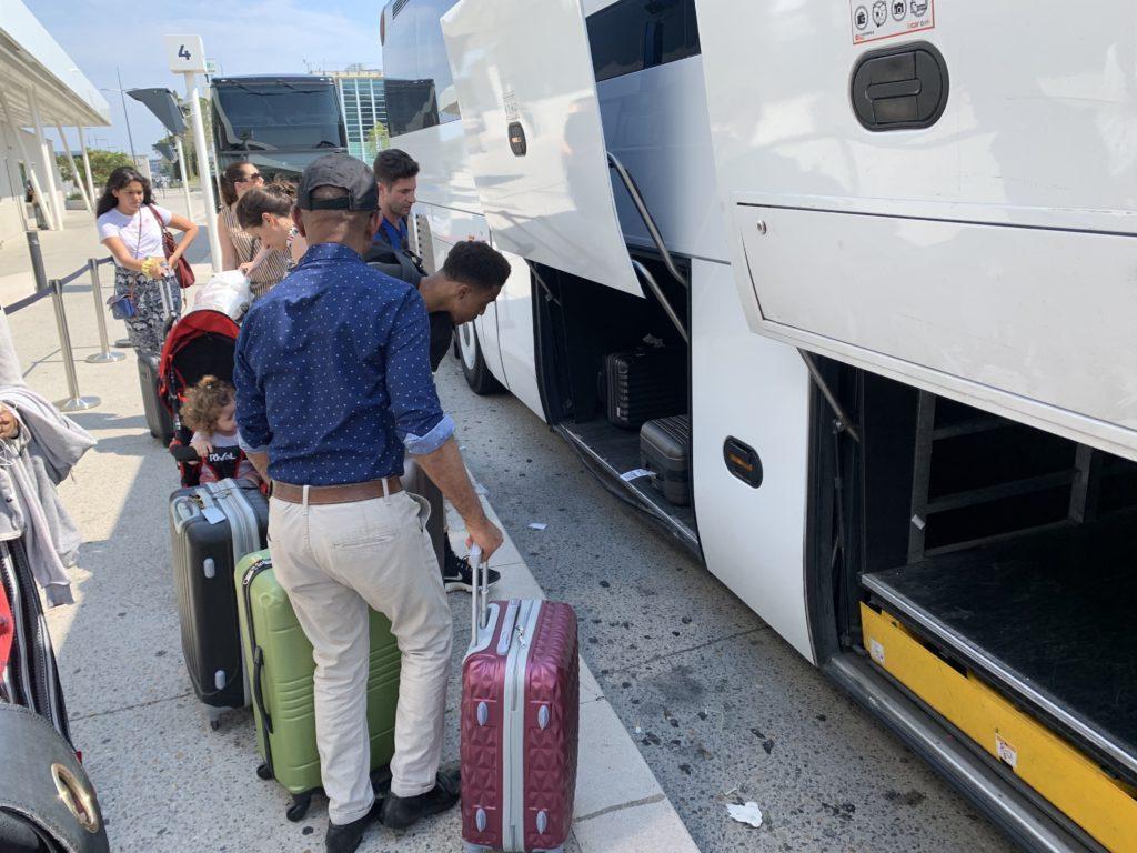 エアポートバスにスーツケースを積み込む人たち