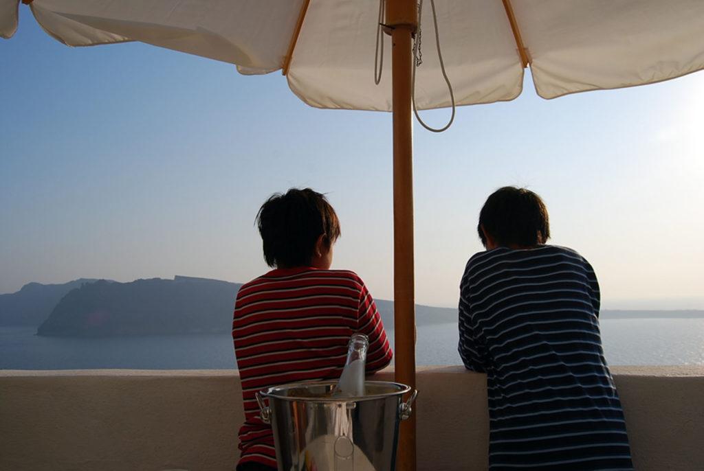 ホテルから夕方のエーゲ海を眺める子供達