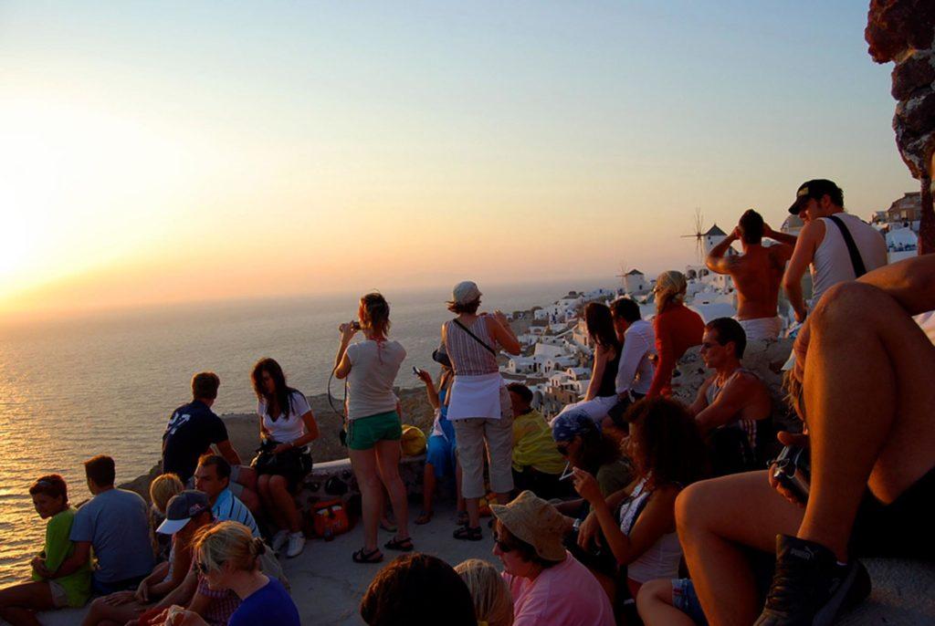 イアの町から夕日を眺める大勢の観光客