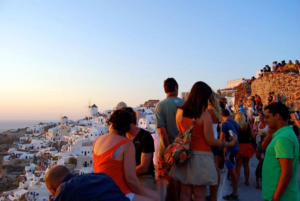 サントリーニ島イアの世界一の夕日を見るために場所取りをする大勢の観光客