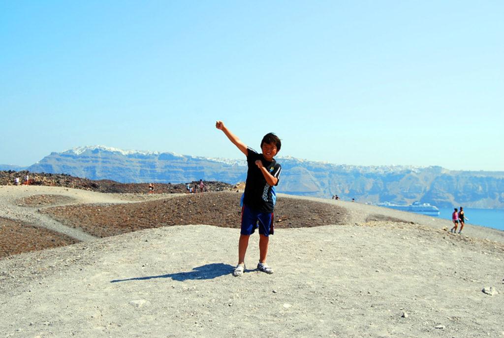海の向こうに見えるフィラをバックに火山島の頂上で次男の記念撮影