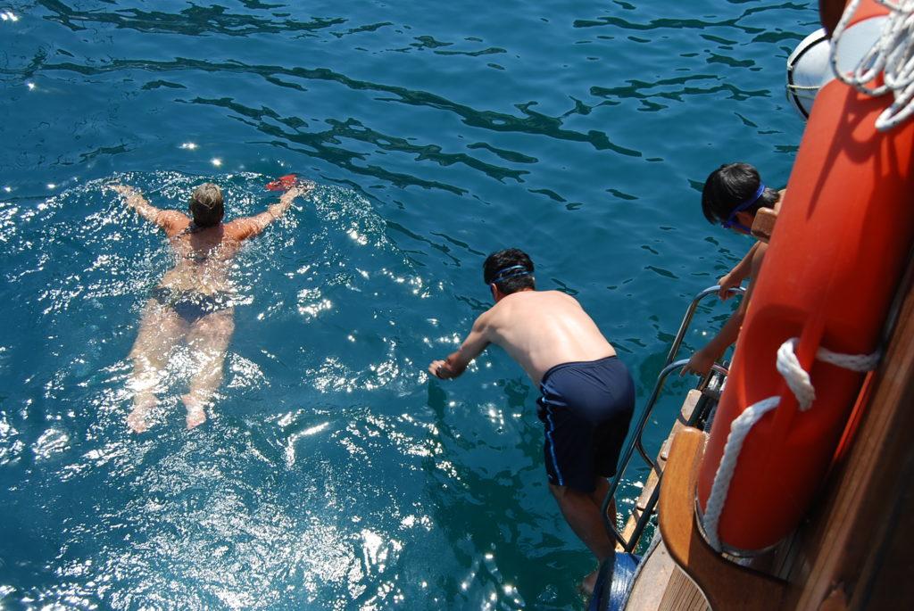 海中天然温泉にむかって船から飛び込む私と子供