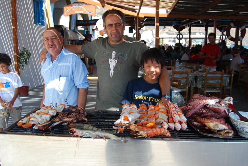 ティラシア島レストランでお店のオーナーやスタッフと長男の記念写真