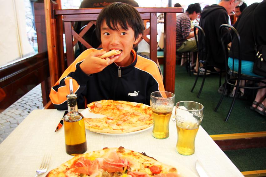 ソーセージのピザを美味しそうに食べる次男