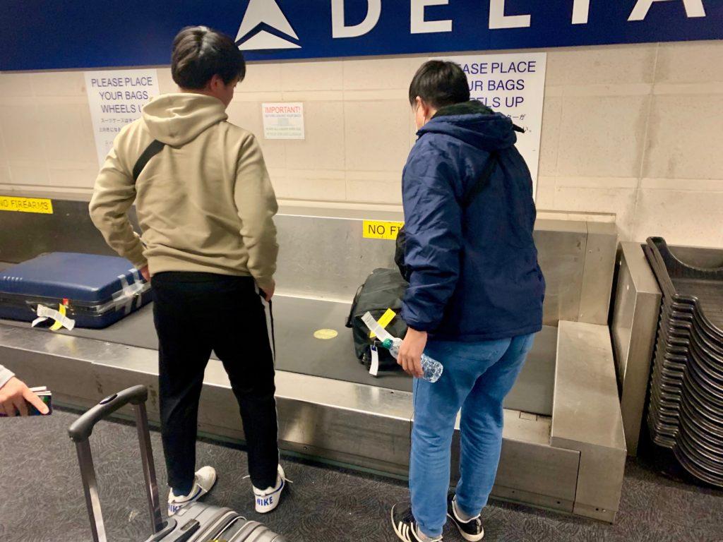 スーツケースを台の上に置く長男と次男