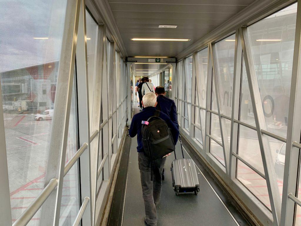 飛行機とターミナルビルを繋ぐブリッジを渡る旅客