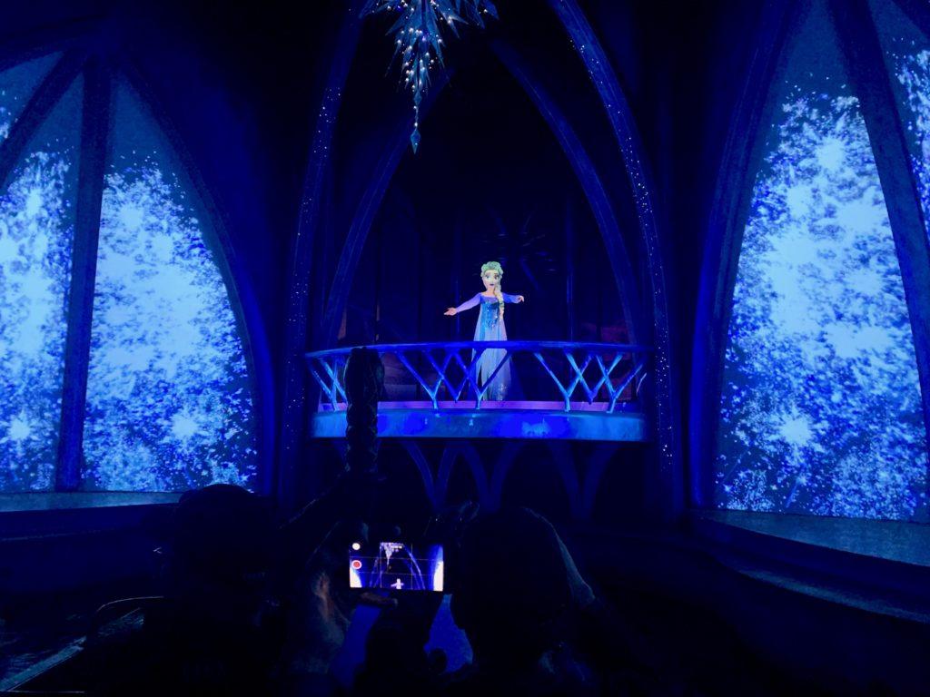 氷の城のバルコニーでゲストを出迎えるエルサ