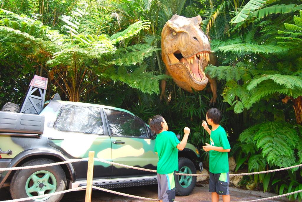 ジャングルの茂みから顔を出す恐竜に驚く子どもたち