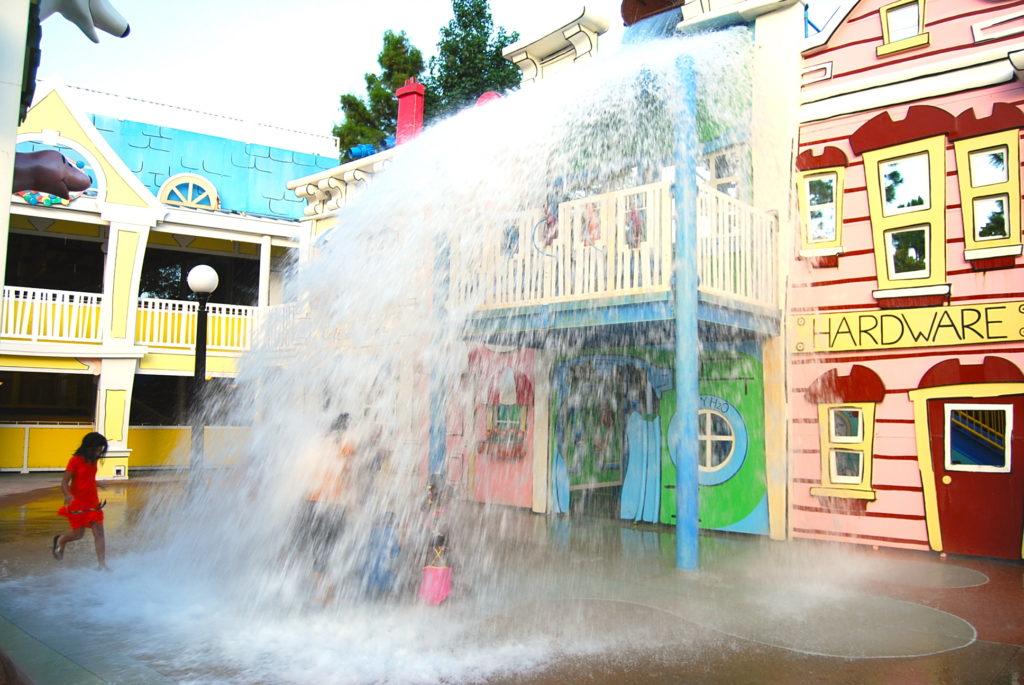 キュリアス・ジョージ・ゴーズ・トゥー・タウンの水の仕掛けで喜ぶ子供たち