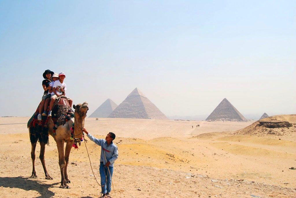 世界遺産ギザのピラミッドを背景にラクダに乗っているママと子供達