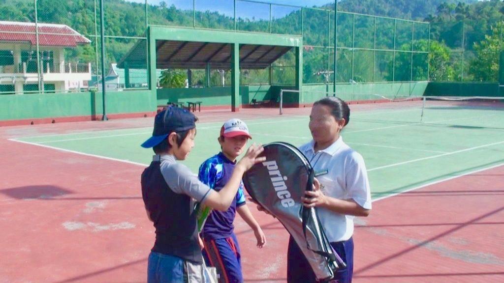 テニスコートでラケットを受け取る長男