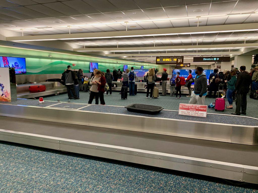 バゲージクレームで荷物が出てくるのを待つ旅客たち