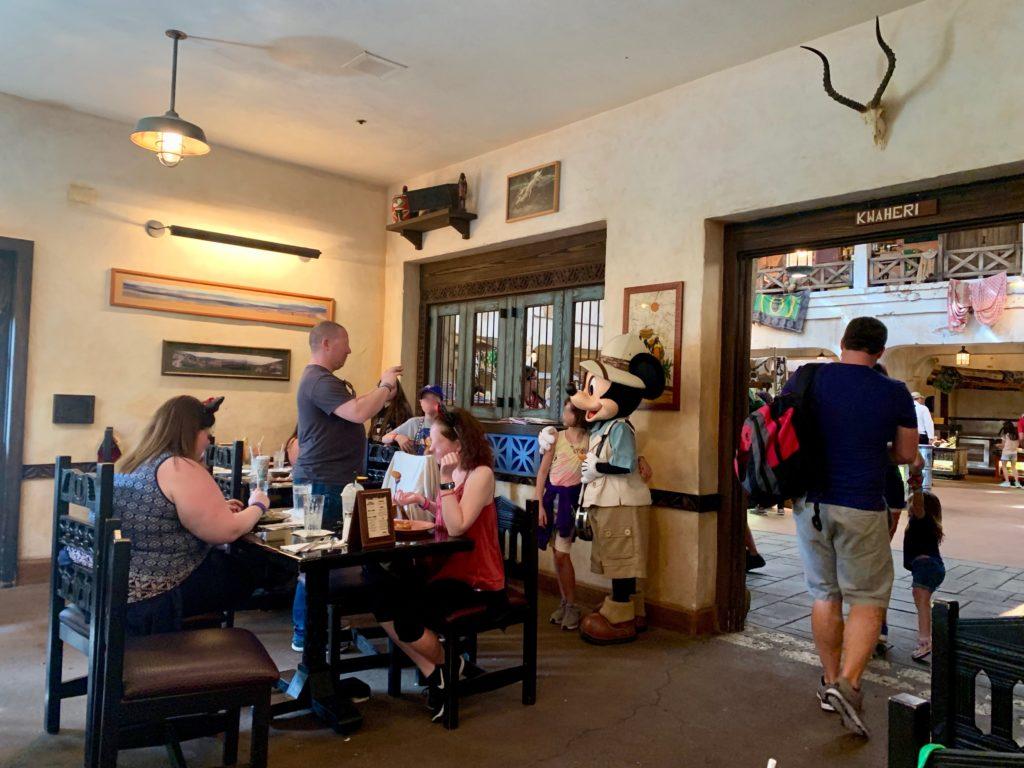 タスカーハウスレストランでミッキーマウスと写真を撮るゲストたち