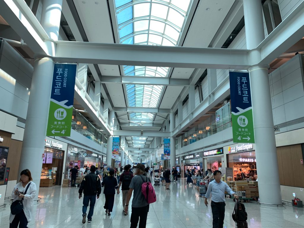 ソウル・インチョン空港で乗継ぎエリアを歩く人たち