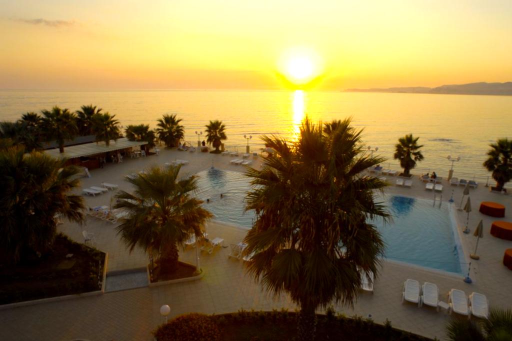 ディオスクリベイ・パラス・ホテルのプールから見える海に沈む夕日