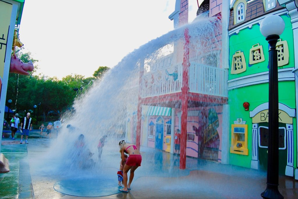 キュリアス・ジョージ・ゴーズ・トゥ・タウンで水遊びする子連れファミリー