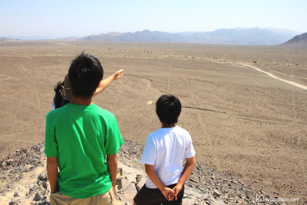 頂上でロサさんの説明を聞きながらナスカの線を見る子供達