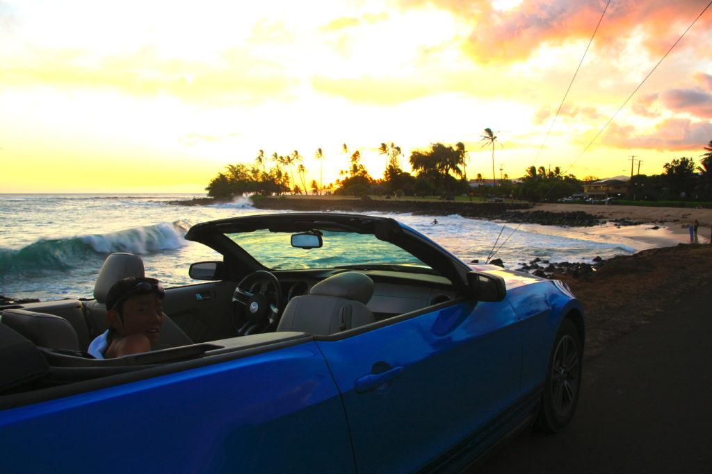 カウアイ島の夕方のビーチでオープンカーに乗って振り向く次男
