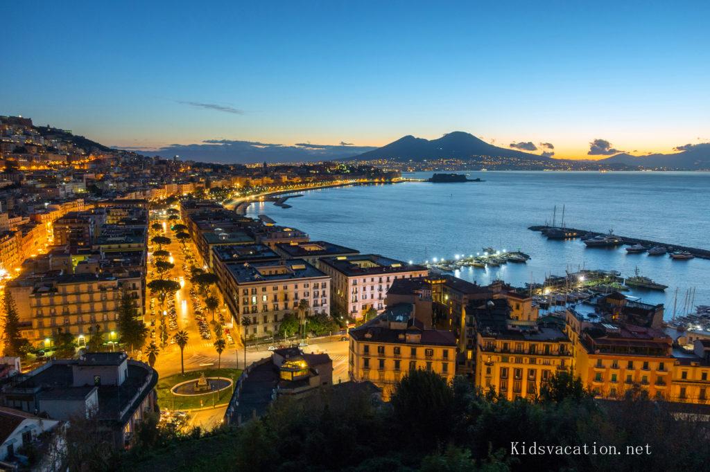 ライトアップされたナポリの街と夕景のナポリ湾腰に見えるヴェスヴィオ火山