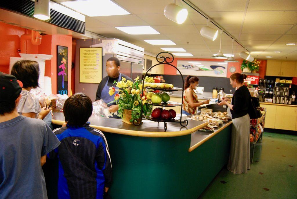 カフェテリアでサンドイッチを買うママと子供たち
