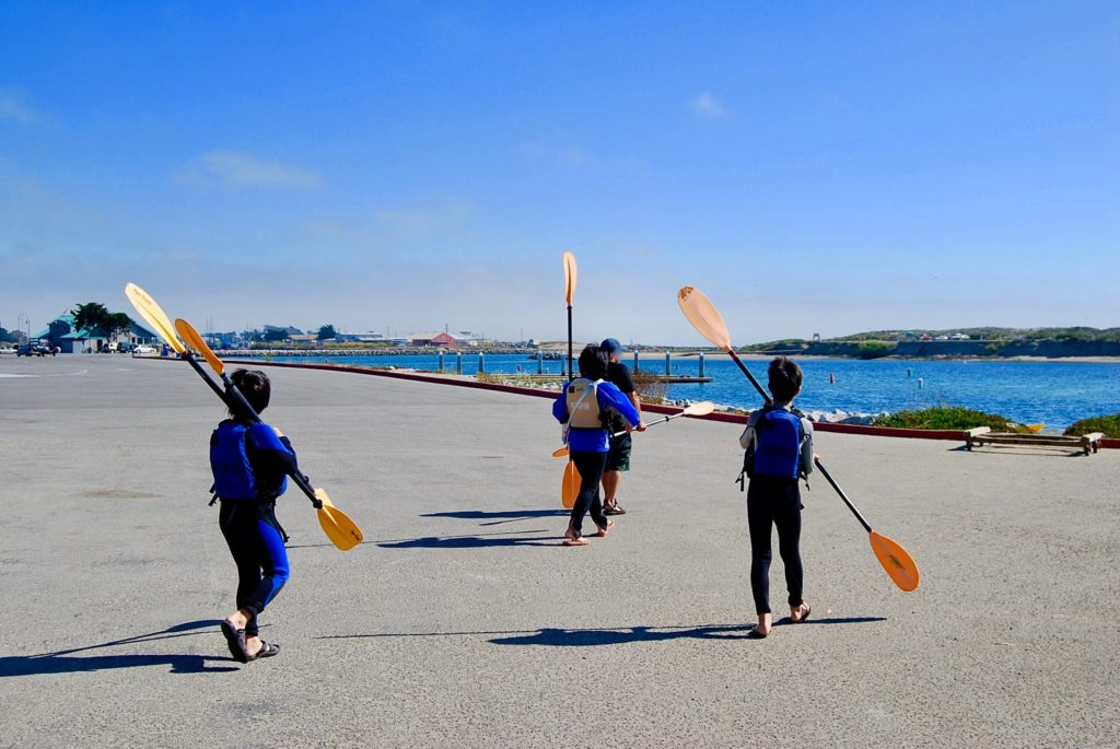 カヤックのパドルを持って海の方へ歩く子供たち