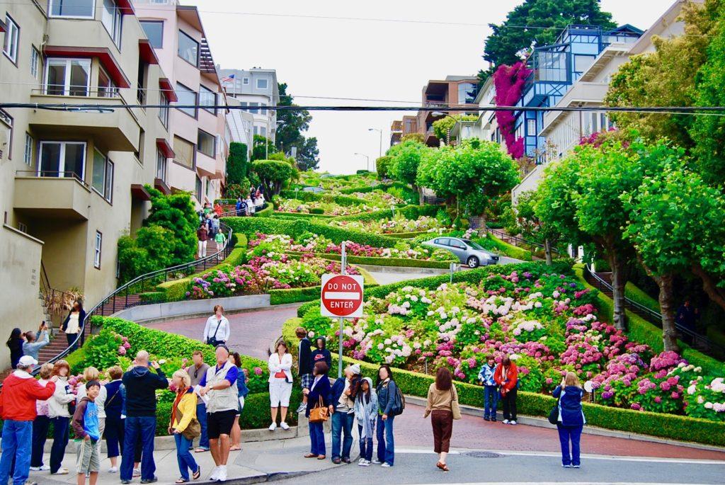 坂の下でロンバードストリートを背景に写真撮影をする観光客