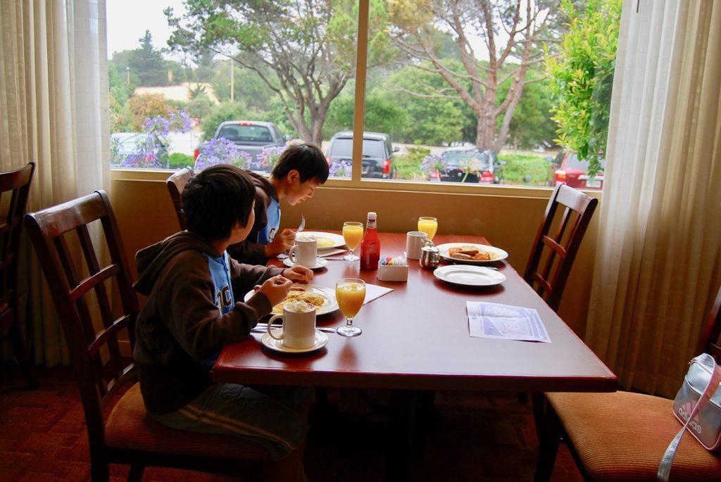 窓際のテーブル席で朝食を食べる子供たち