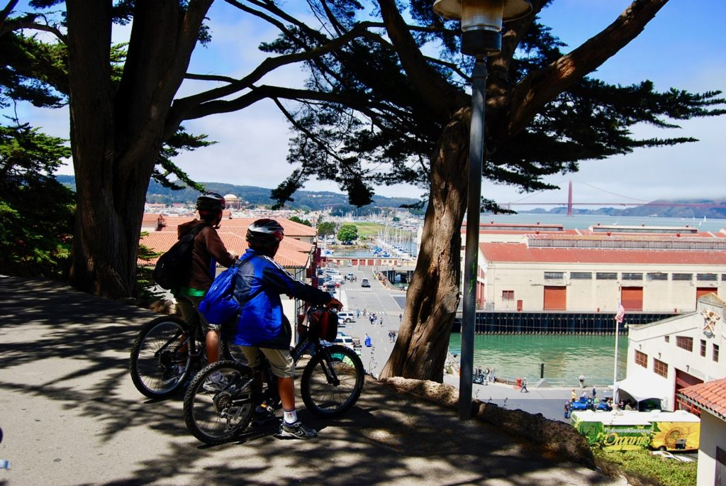 自転車にまたがり丘の上からゴールデンゲートブリッジを見る子供達